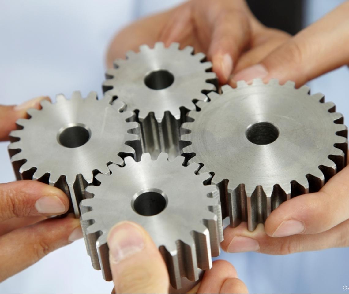 Hands holding four cog wheels together